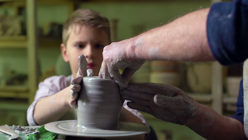 Diligent pupil shaping a pot under the guidance of his teacher