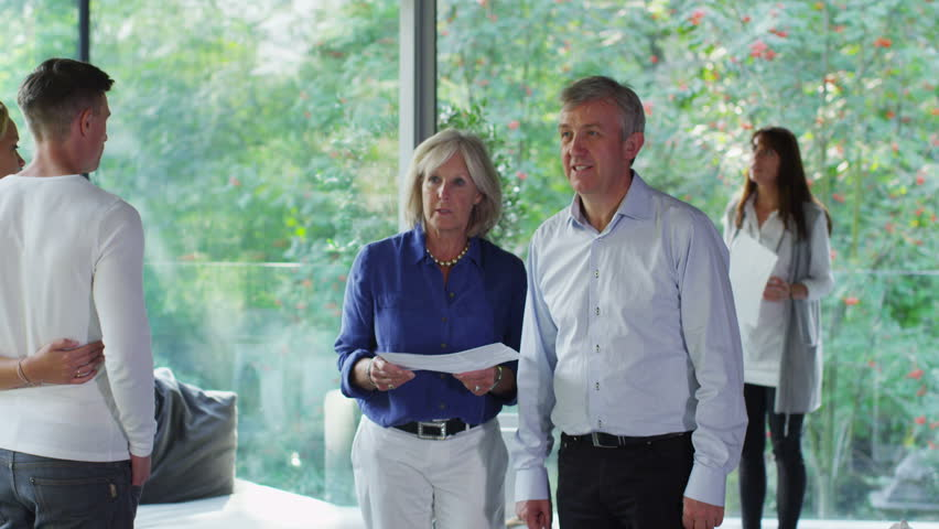 Mature couple talking to estate agent at open viewing of luxury modern home