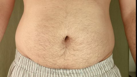 Young Man shakes Fat Belly. Young Adult in pijama pants shakes his fat belly. Front shot.