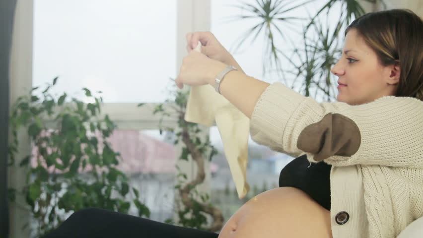 Beautiful pregnant young woman holding up new baby clothes