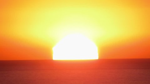 A time lapse of the large orange sunset as the massive sun sets into the horizon above the ocean