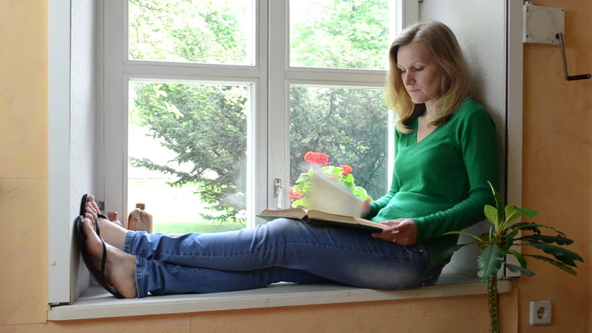 serious face woman sit on windowsill watch through window and read book. -  HD stock