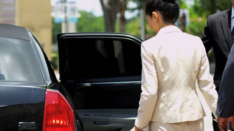 Close up male female business travelers returning from business travel getting into luxury limousine transport driver holding door shot on RED EPIC, 4K, UHD, Ultra HD resolution