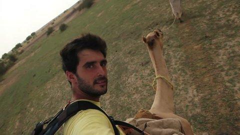 Tourist riding a camel on desert