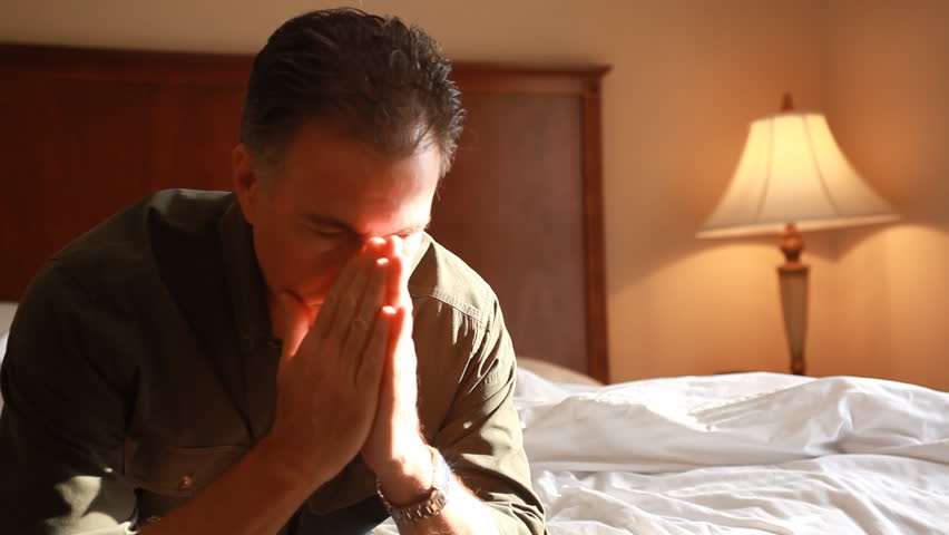 A man in a hotel room who appears to be troubled or anxious about something.