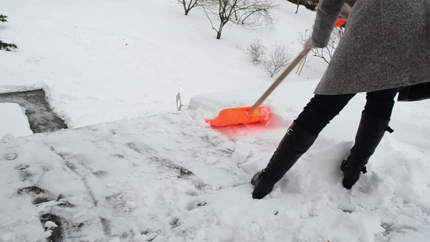 Poor Lonely Woman On Heel And Grey Coat Clean Snow With Orange Shovel From  House Roof