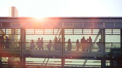 people silhouette walking. group team together. intro. sunset sun flare. modern glass building