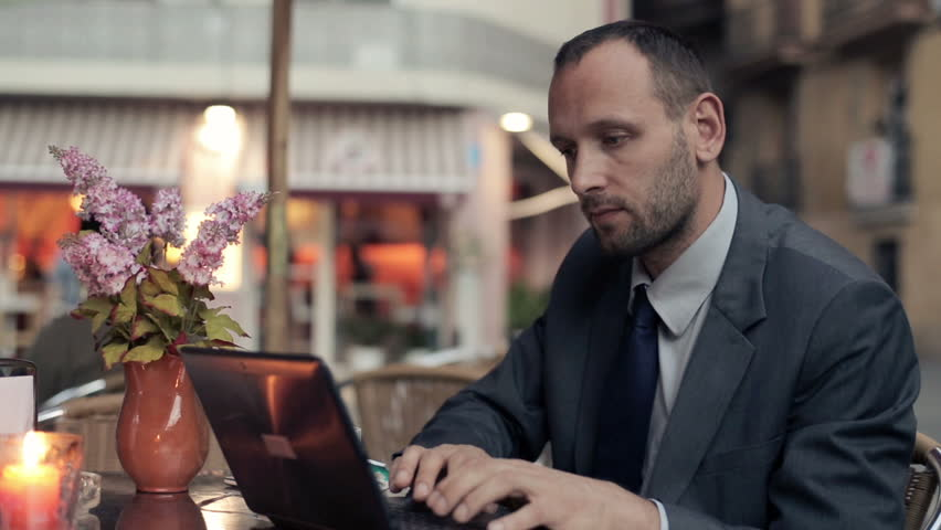 Businessman with modern tablet computer drinking coffee at the cafe