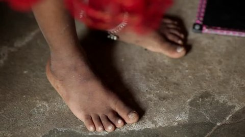 A closeup shot of a young Indian girl's feet moving and dancing against the stone floor. She wears an anklet and red dress.