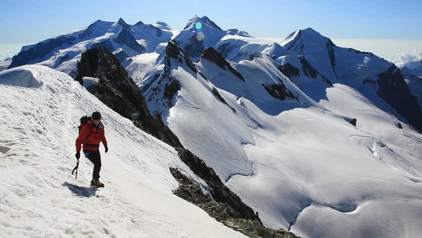 Mountaineer walks along the snowy ridge of Breithorn, exactly on the swiss-italian border. In background the peaks around Zermatt with the Weisshorn. Switzerland, Europe. - HD1080p   Shutterstock HD Video #5370785