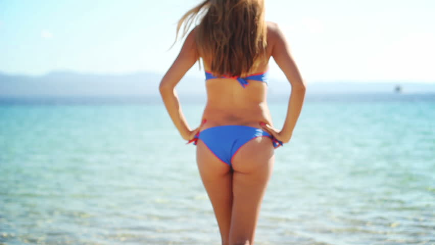 Sexy summer girl - Young woman in a blue and orange bikini slowly walking towards the water, Mediterranean beach on a sunny summer day