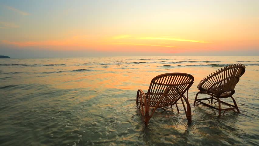 Sunset On A Beach Two Empty Wooden Chairs Standing In A Water