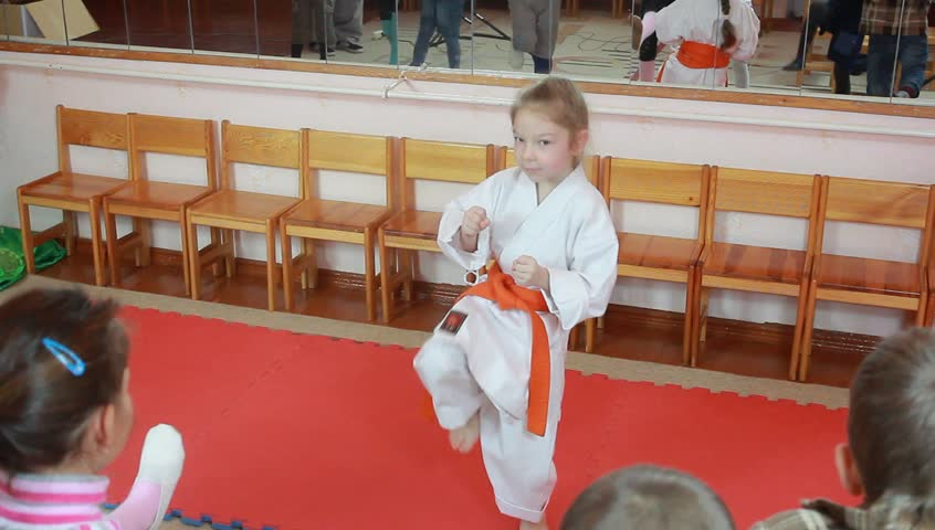 Girl with an orange belt is beating blow foot before the order