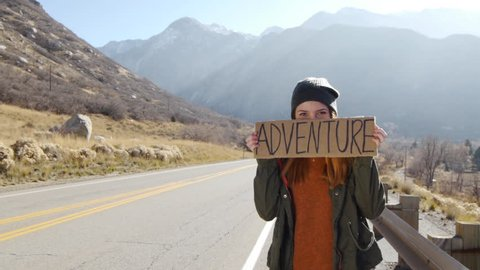Teenage Girl Holding An Adventure Sign On A Mountain Road, Smiles And Laughs