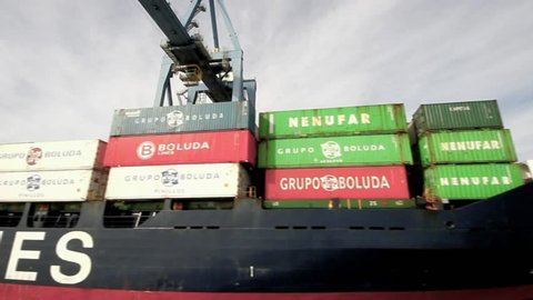 """ALICANTE, SPAIN - JANUARY 16: The containership """"Beatriz B"""" of Boluda Lines Ships works unloading container helped by special crane in Alicante harbor, on january 16, 2014 in Alicante."""