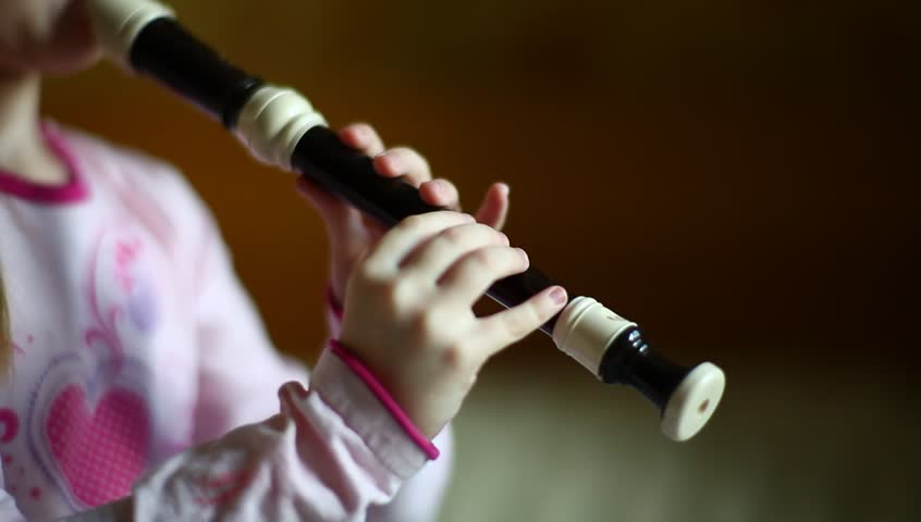 little girl playing flute (English flute, recorder, blockflute), beautiful macro shot with soft focus