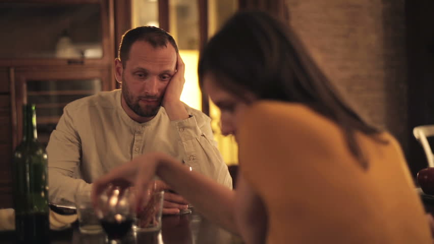 Offended man sitting by the table with boyfriend at home