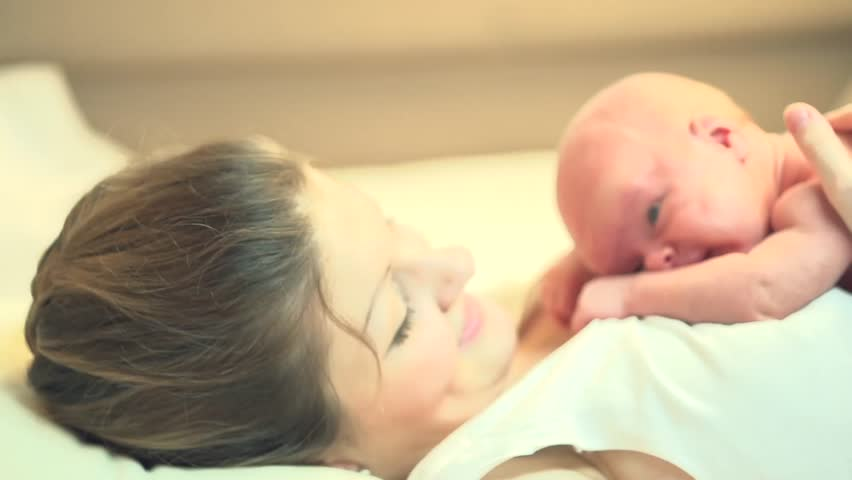 Mother and her Newborn Baby. Happy Mother and Baby kissing and hugging. Resting in bed together. Maternity concept. Parenthood. Motherhood   Beautiful Happy Family Stock Video Footage. Slow Motion | Shutterstock HD Video #5446799