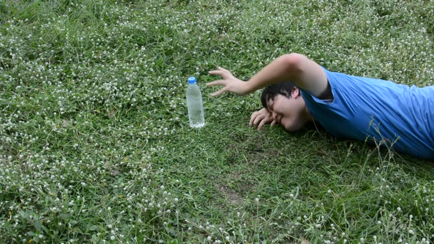 Asian Thai male guy is struggling crawling for a plastic drinking water bottle to survive his thirst and heatstroke on the empty green grass field but couldn't make it. It's a death concept.