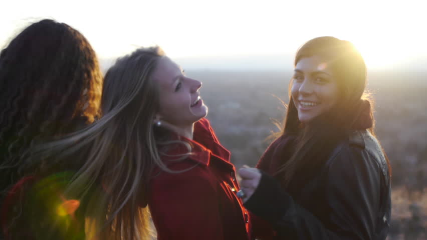 Smiling Teens Turn For A Sunset View