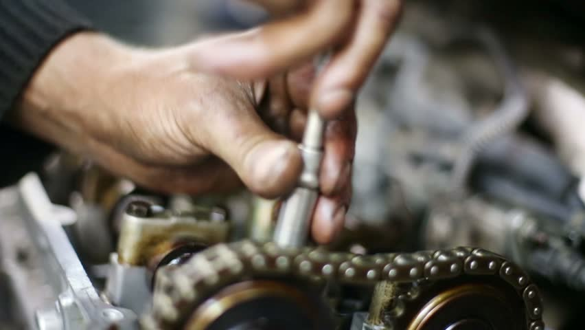 Mechanic hands unscrews screw by screwdriver of gasoline car motor