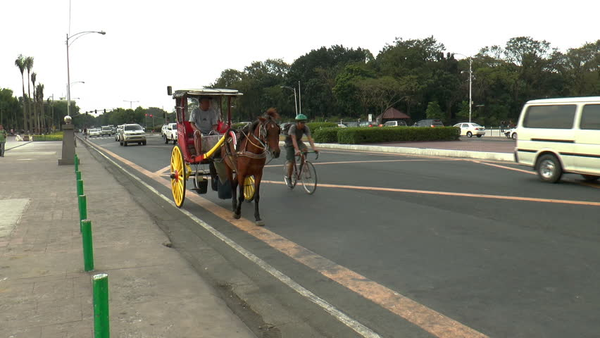 MANILA, PH - JANUARY 22: Horse-drawn carriage, and cars passing a not too busy street front of Rizal park in Manila Philippines on January 22, 2014.  | Shutterstock HD Video #5482439