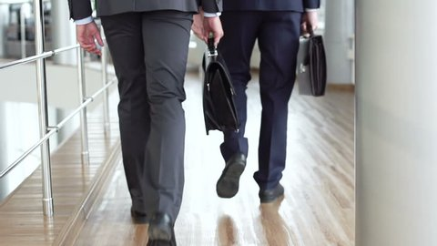 Elegant businessmen viewed from behind walking together across the office building