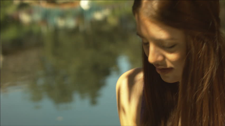 Beautiful girl by a pond, looking around | Shutterstock HD Video #5504915