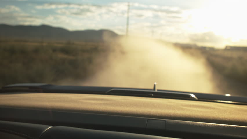 Car speeding down a dusty dirt road, close-up of a teen latina in the backseat