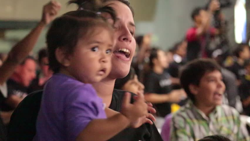 Cali, Columbia, SA - Circa 2013: A young Latino woman holds her little girl and dances in anticipation for the church concert to begin in Cali, Columbia, South America, Circa 2013.