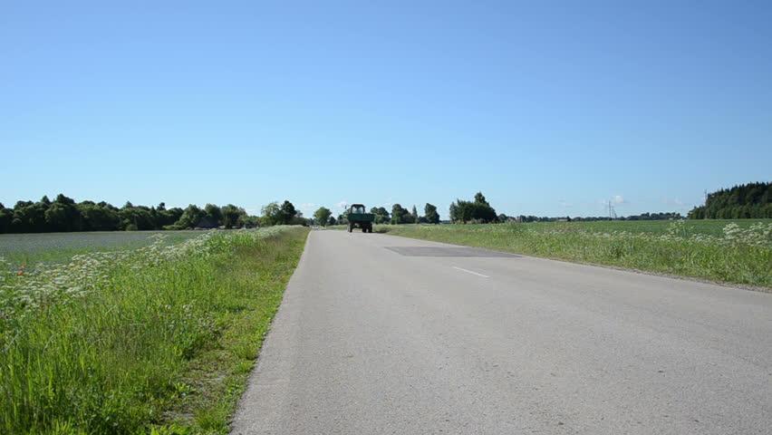 Tractor with trailer drive on rural asphalt road near cornflower field. | Shutterstock HD Video #5528615