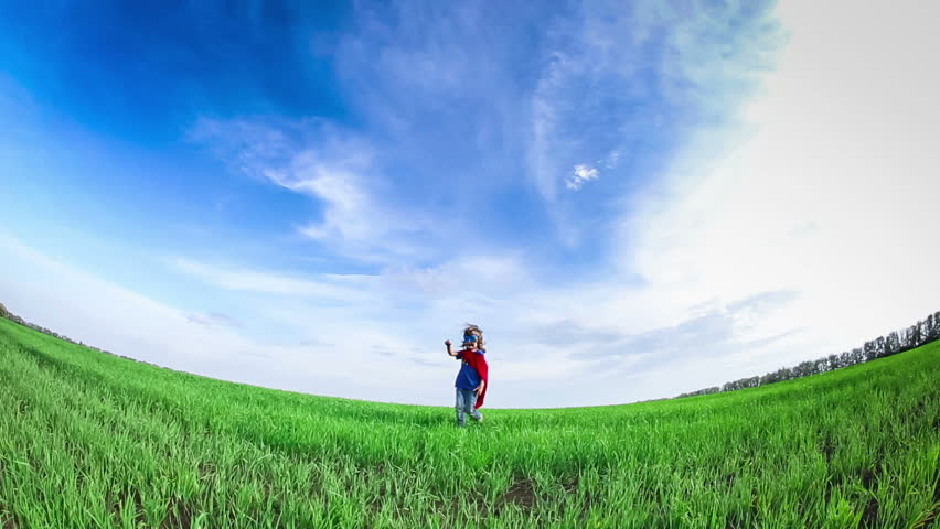 Superhero kid running in green field against blue summer sky