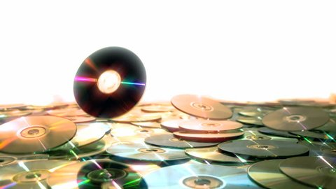 Optical Discs falling onto big pile of DVDs or CDs