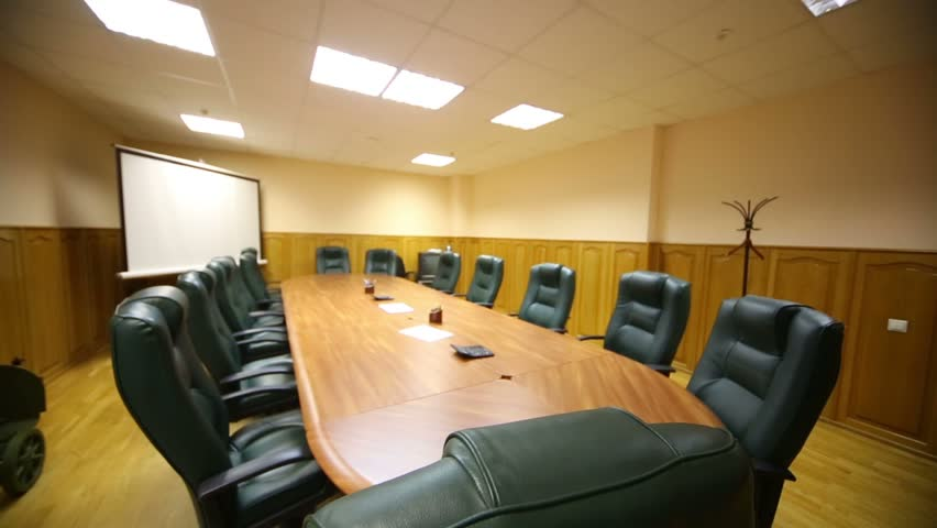 Long wooden table, leather armchairs in empty room for business meetings