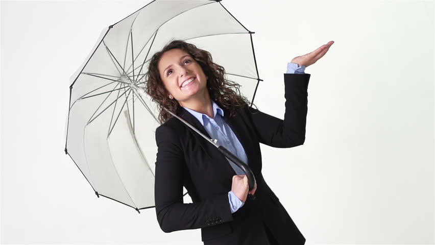 Happy girl in business suit hiding from a pouring money rain under umbrella slow motion