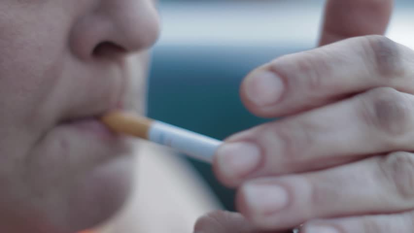 Close-up of a woman lighting a cigarette and inhaling. | Shutterstock HD Video #5560649