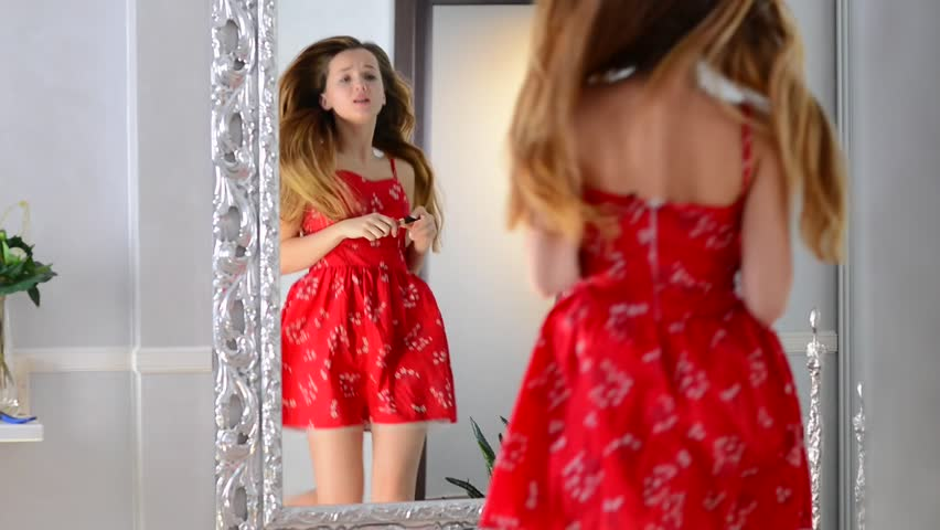 Beauty Teenage Girl in red dress applying Make up and admiring herself in the mirror. Beautiful Teenager Looking in the Mirror at home, singing and putting makeup on. Teen Fashion 1080p