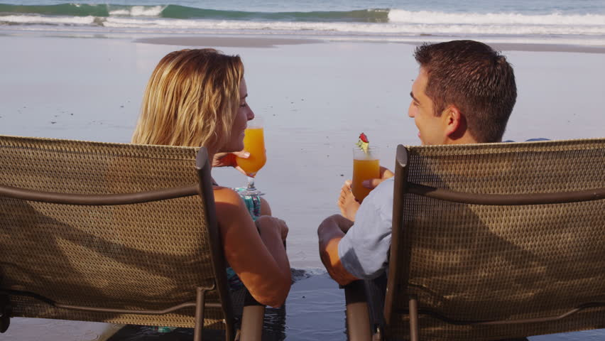 Couple with tropical cocktails at beach. Shot on RED EPIC for high quality 4K, UHD, Ultra HD resolution.