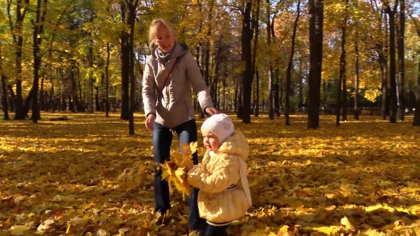 Mom and daughter throw up yellow leaves in sunny autumn park. Flycam, Slow Motion.