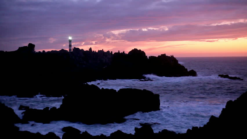beautiful sunset on coastline with powerful lighted lighthouse, ouessant island, brittany, france