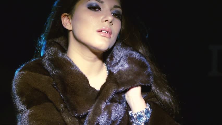 Beauty Fashion Model Girl in Mink Fur Coat. Beautiful Woman in Luxury Black Fur Jacket. Winter Fashion, Blowing Hair in the snow. Over black background. 1920x1080 HD video footage