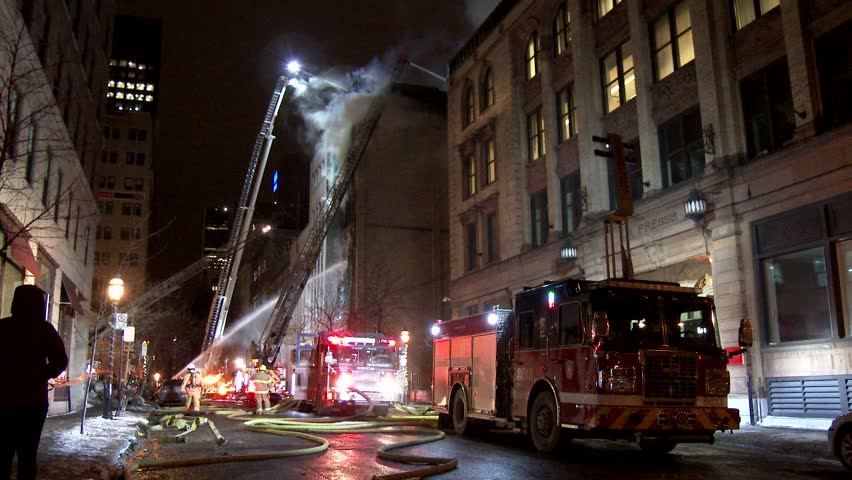 MONTREAL, QC - 1/2014 - 4K 60fps - Fire ladders attacking building fire. Wide angle shot of trucks and ladders spraying water on a building fire with smoke showing in old architecture style city setup