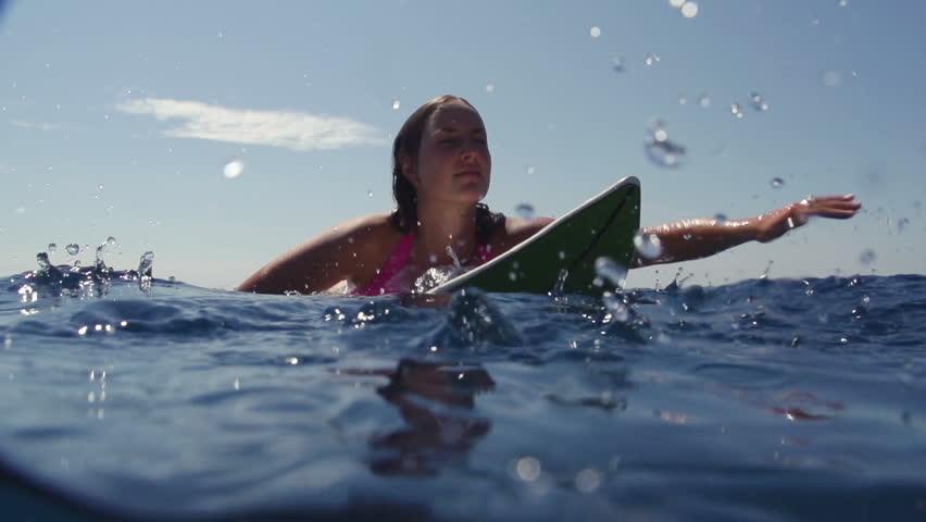 SLOW MOTION: Female surfer paddling