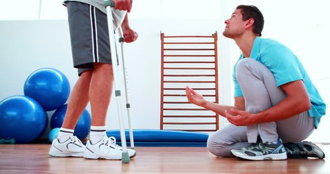 Physiotherapist helping patient walk with crutches at the rehabilitation center