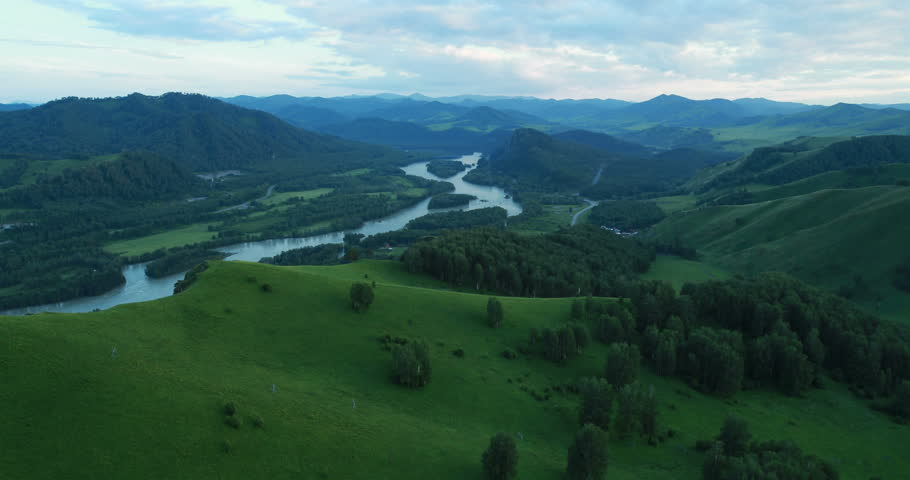Aerial View. Flight over a green grassy rocky hills. Altai Mountains, Siberia, Russia. Summer 2013