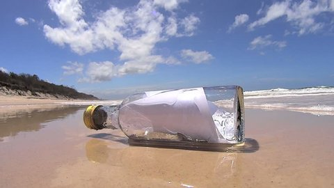 Wave comes in and washes a bottle with a message in it into the lens of the camera.