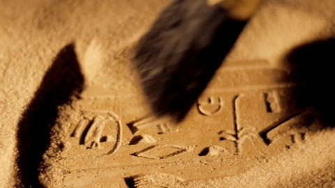 Tracking shot of archaeologist brushing sand from ancient Egyptian hieroglyphics