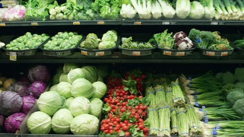 Wide shot moving past fresh vegetables in a supermarket grocery. Includes cabbage, celery, broccoli, lettuce, carrots, corn, onion, etc. Medium shot and close-up of same set-up are in my portfolio.