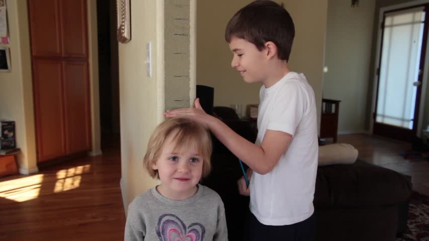 Big Brother Measures Little Sister's Height against the wall.  | Shutterstock HD Video #5702795