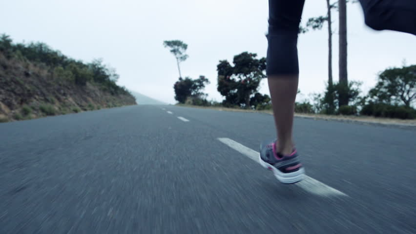 woman running on road close up shoes steadicam shot #5713925